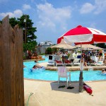 Lifeguard stand with red and white umbrella looks over pool at waterpark