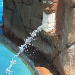 Tiki head squirts water at waterpark pool