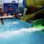 Water splashes from waterslide as woman waits in the pool
