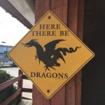 Yellow sign warning of dragons at mini golf course