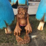 Troll statue with big hands and feet at mini golf course