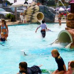 Young children playfully playing in waterpark pool