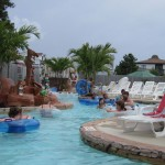 Families swim in waterpark pool using rafts