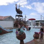 Families play under an adventure shower at waterpark