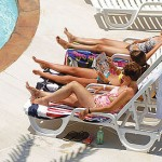 Young women lounge poolside on chairs