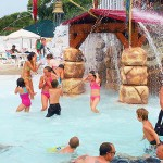 Young girls play under waterfall at waterpark