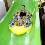 Daughter and mother slide down waterpark waterslide