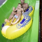 Father and son slide down waterpark waterslide