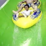 Son and father slide down waterslide at waterpark