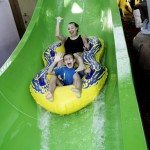 Mother and son wave hi as sliding down waterslide at waterpark