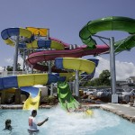 Son and father come out of waterslide making big splash