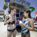 Two girls eat snowballs on the beach in Ocean City