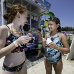 Girls eat icecream as boy orders icecream at waterpark