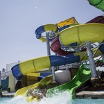 Woman holds on to raft as she splashes from waterslide