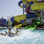 Two sisters splash from waterpark waterslide