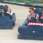 Two dads and daughters ride black go karts together