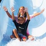 Mother and son slide down waterslide with hands up