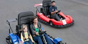 two go carts one with man one with woman and daughter