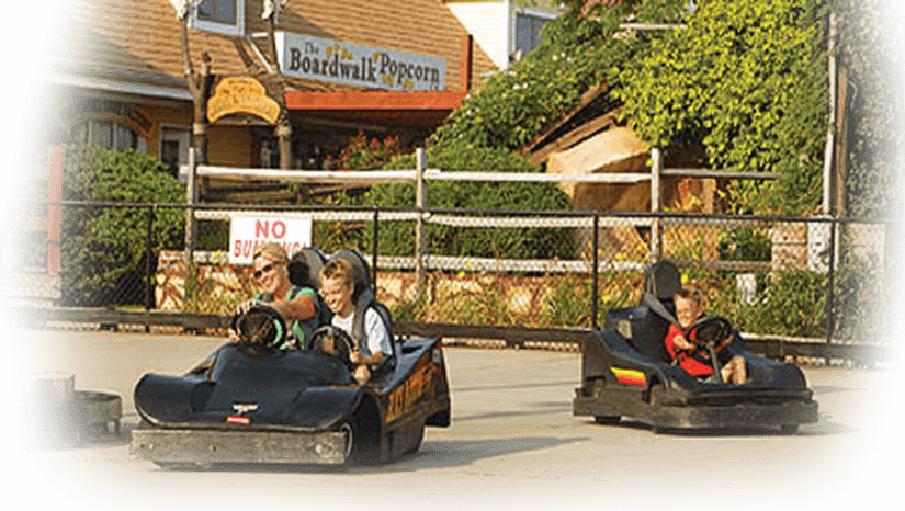 Young boy and mother driving go kart in Ocean City