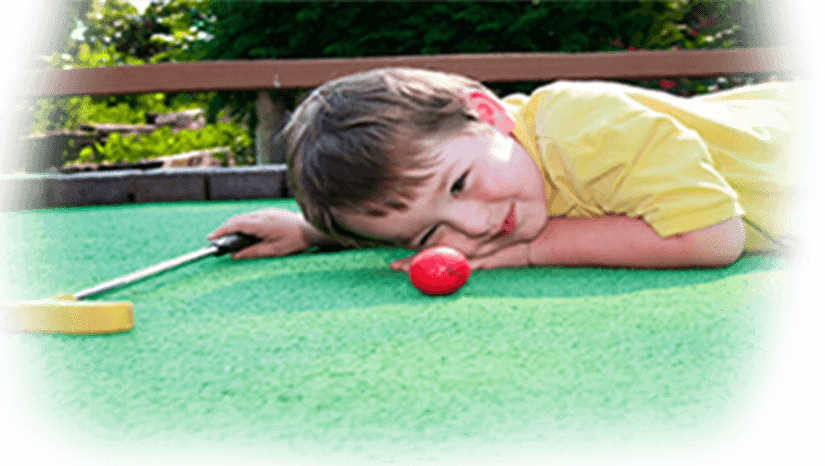 Young boy eyeballing the ball shot at miniature golf