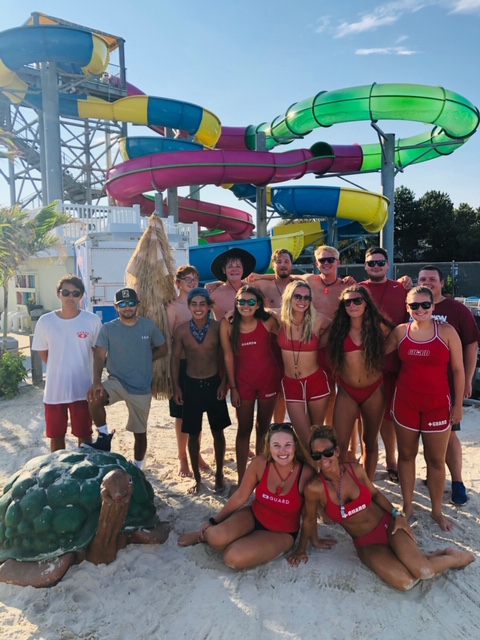 employees of waterpark standing in front of water slides posing for a picture